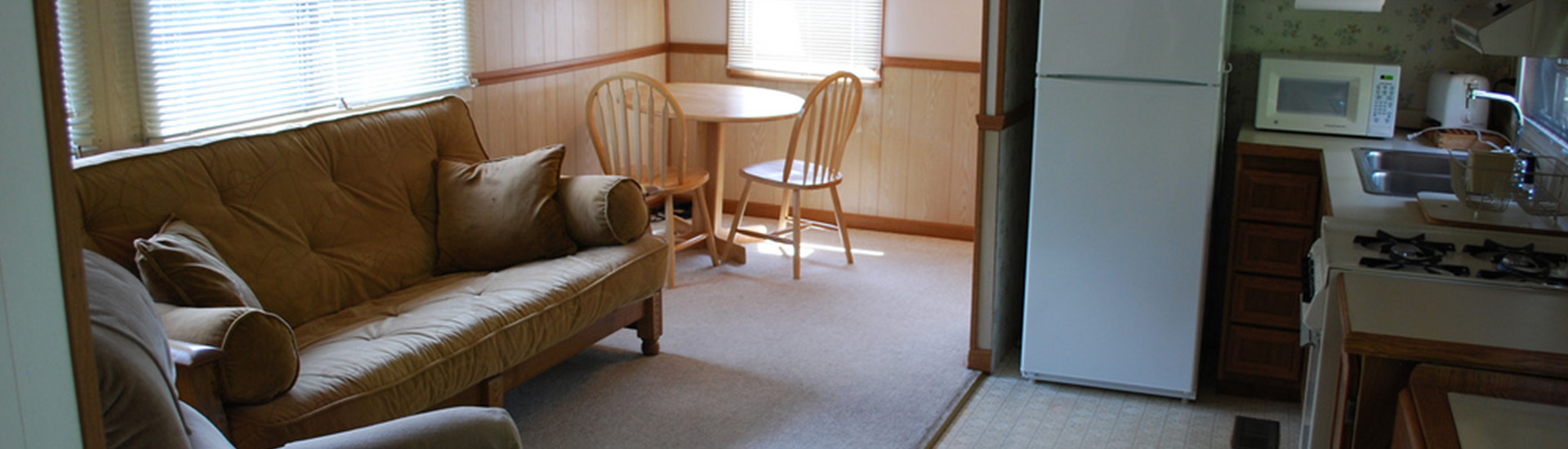 Inside of a cottage, with a sofa on the left, a table and chairs nearby, and the kitchen to the right.